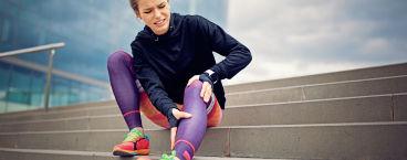 jovem mulher sentada numa escada com dor no joelho