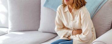 mulher no sofá com dores no estômago