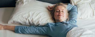 mulher sorridente deitada na cama a dormir