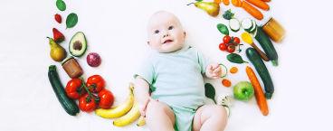 bebé rodeado de alimentos sólidos