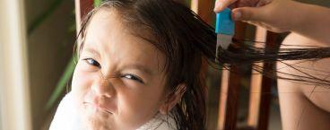 mãe a limpar cabeça de criança com piolhos