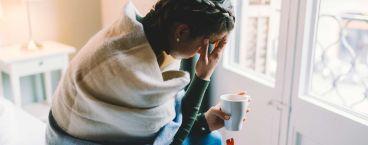 mulher a beber chá e com dores de cabeça