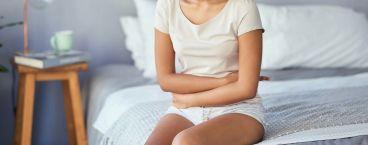 mulher sentada na cama com braços cruzados
