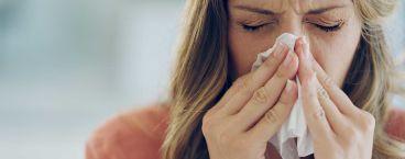 mulher a limpar o nariz com lenço de papel