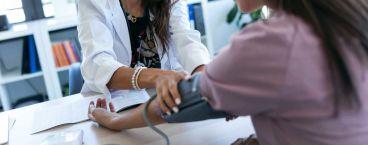 mulher a medir a tensão arterial
