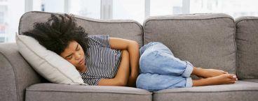 mulher deitada no sofá com dores abdominais