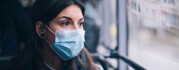 mulher jovem com máscara cirúrgica a olhar pela janela