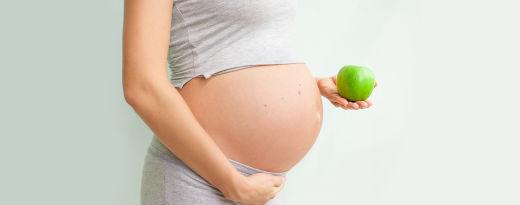grávida com uma maçã na mãográvida com uma maçã na mão