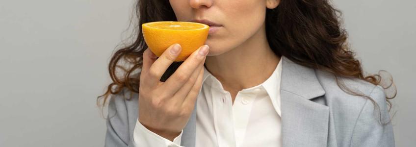 mulher a tentar cheirar uma laranja