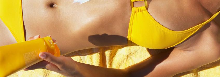 jovem deitada na toalha de praia a aplicar protetor