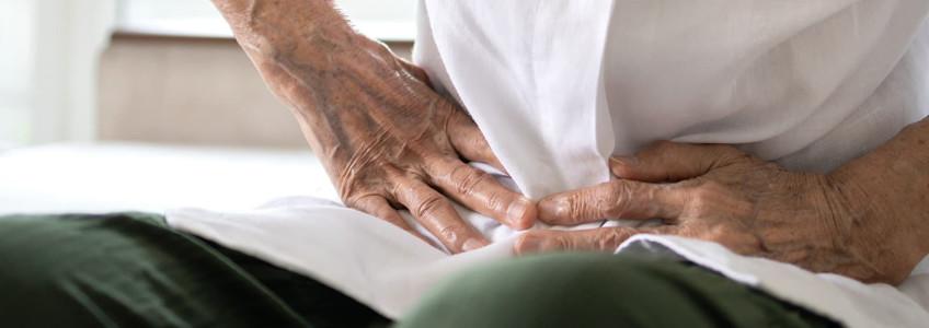 mulher com as mãos a pressionar a zona abdominal