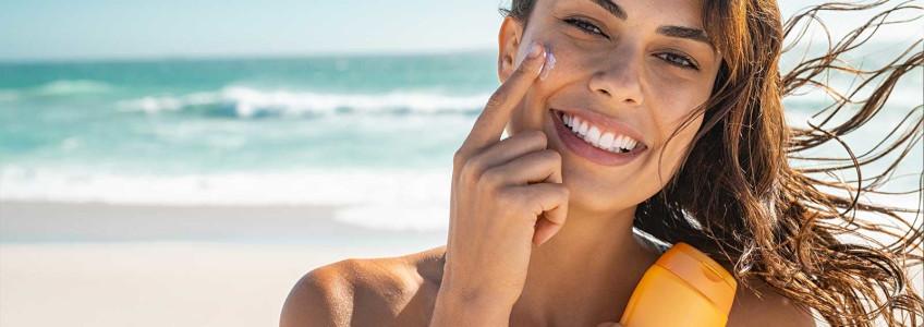 mulher sorridente na praia a aplicar protetor solar