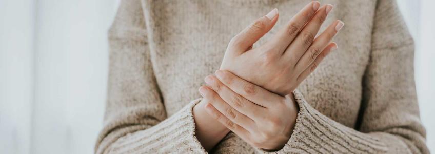 mulher a pressionar a mão com dores