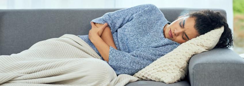 mulher com dores de barriga deitada no sofá