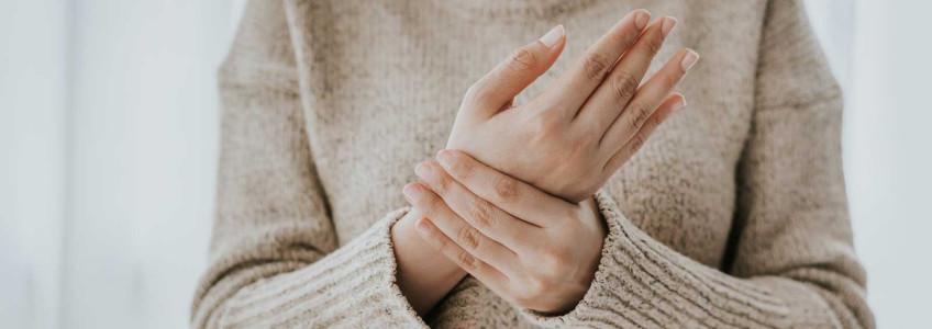 mulher com dores a massajar as mãos